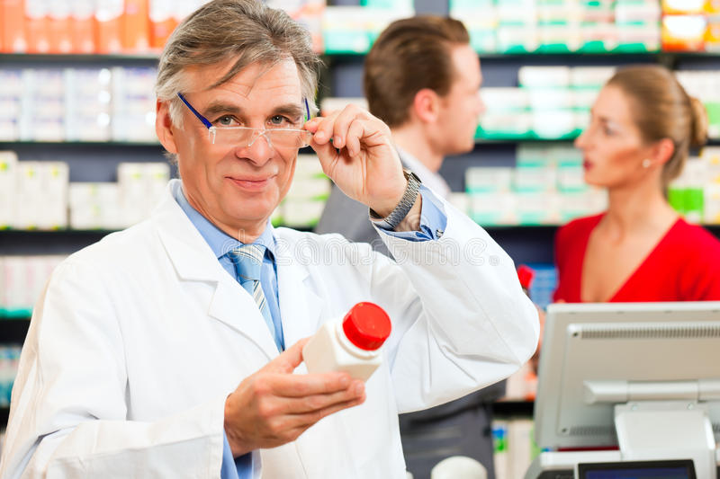 Pharmacist with customers in pharmacy stock image