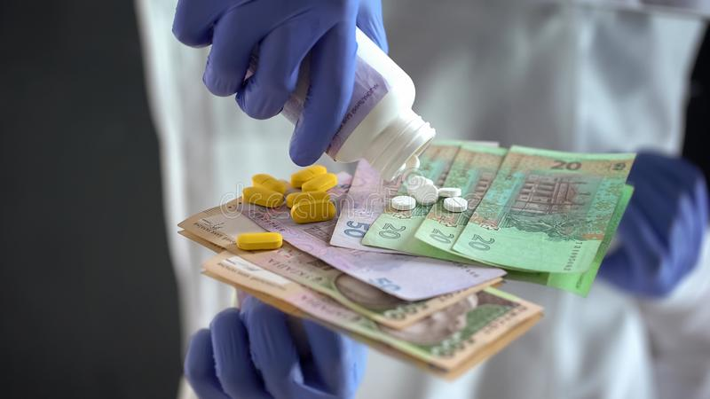 Pharmacist dropping pills on hryvnias, expensive medical treatments in Ukraine. Stock photo royalty free stock photography