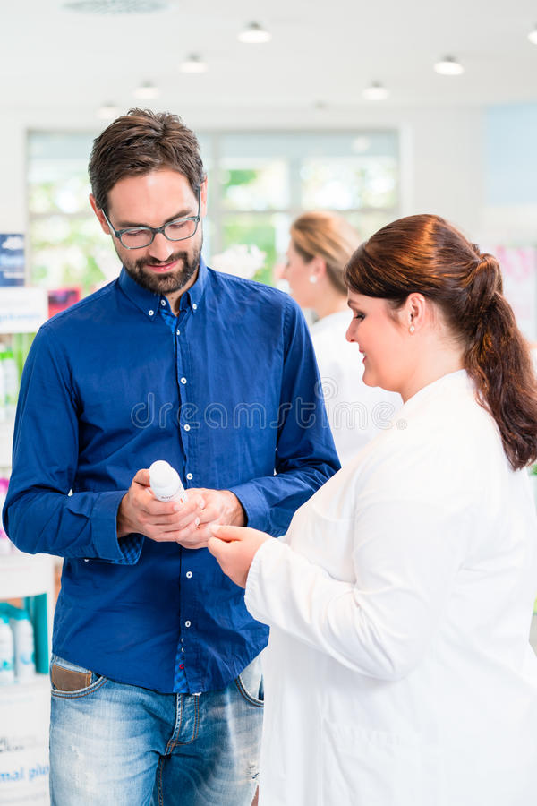 Pharmacist or drug store sales woman advising customer stock images