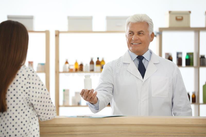 Pharmacist giving medicine to customer in drugsto stock images