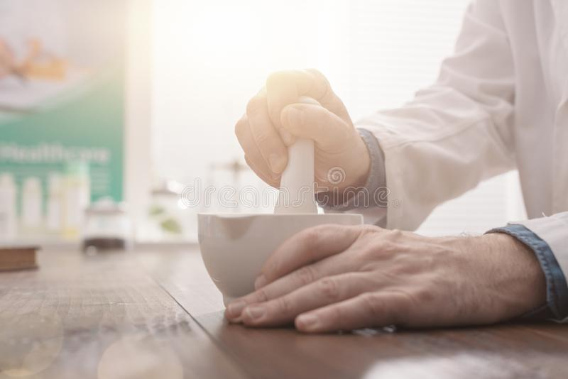 Pharmacist grinding a preparation using a pestle stock photo