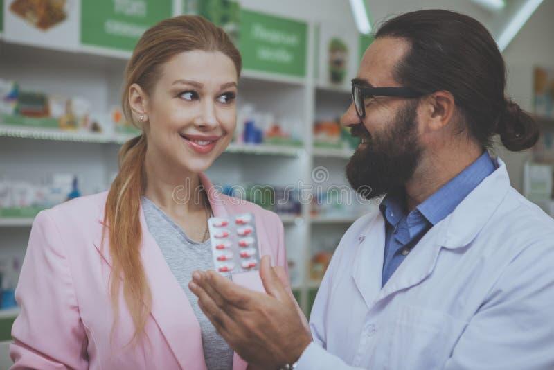 Pharmacist helping his female customer at drugstore stock photos