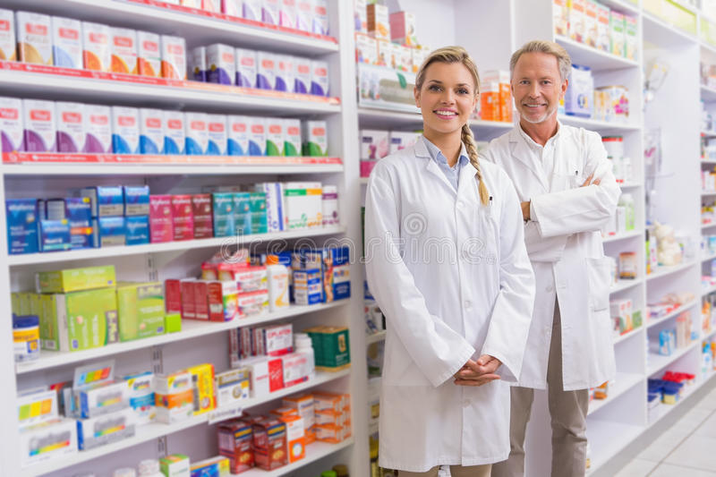 Pharmacist with his trainee standing and smiling at camera. In the pharmacy stock image
