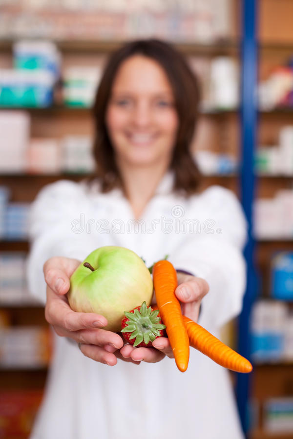 Pharmacist Holding Artificial Carrots; Strawberry And Apple At P stock images