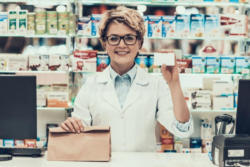 Pharmacist Holding Credit Card and Bag of Medicine stock images