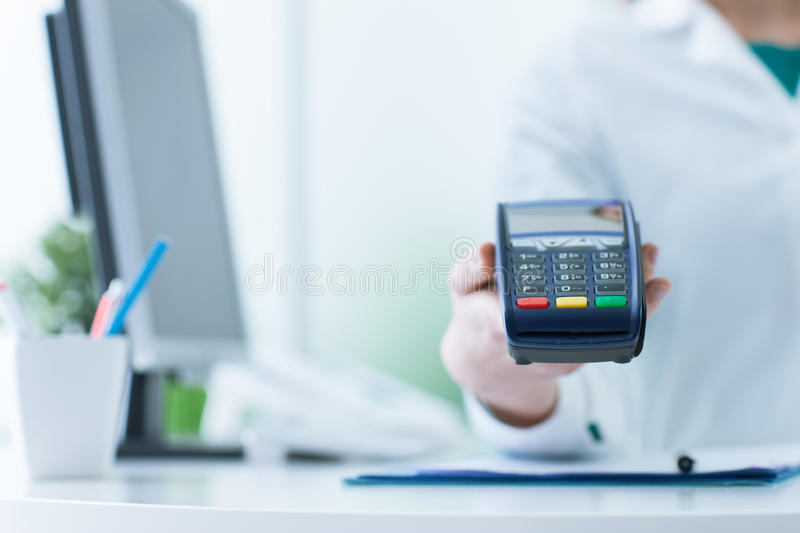 Pharmacist holding a payment terminal stock photos