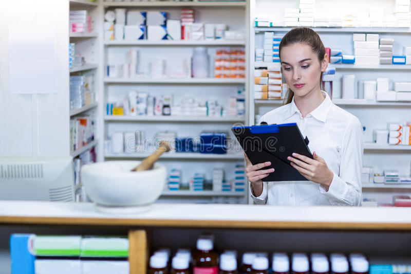 Pharmacist looking in clipboard at counter stock images