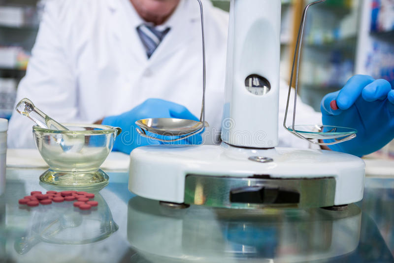 Pharmacist measuring tablets with pharmacy scale royalty free stock images