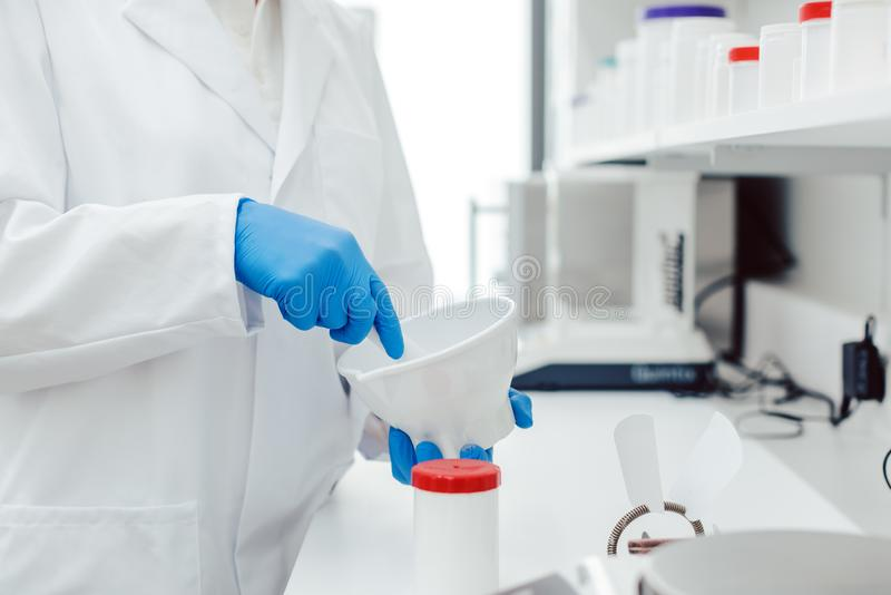 Pharmacist mixing drug on order in laboratory stock photo