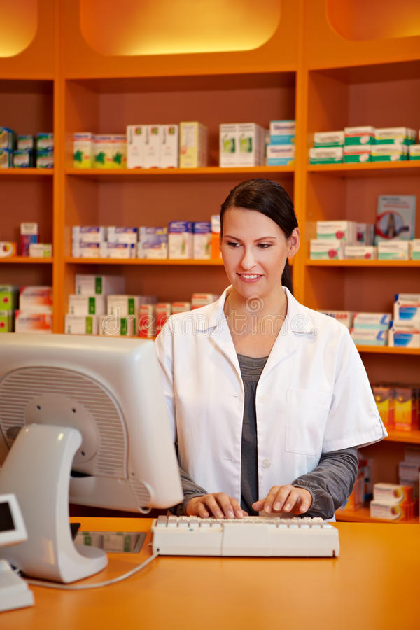 Pharmacist ordering medicine. With computer in a drugstore royalty free stock photos