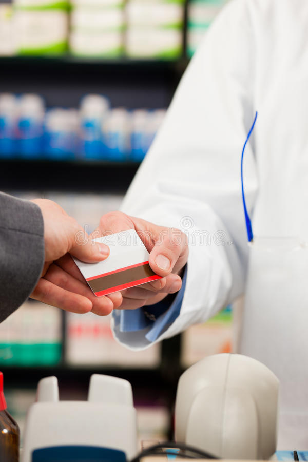 Pharmacist with paying customer in pharmacy. Pharmacist with customer in pharmacy; the customer pays with credit card; from both only the hands are seen royalty free stock photo