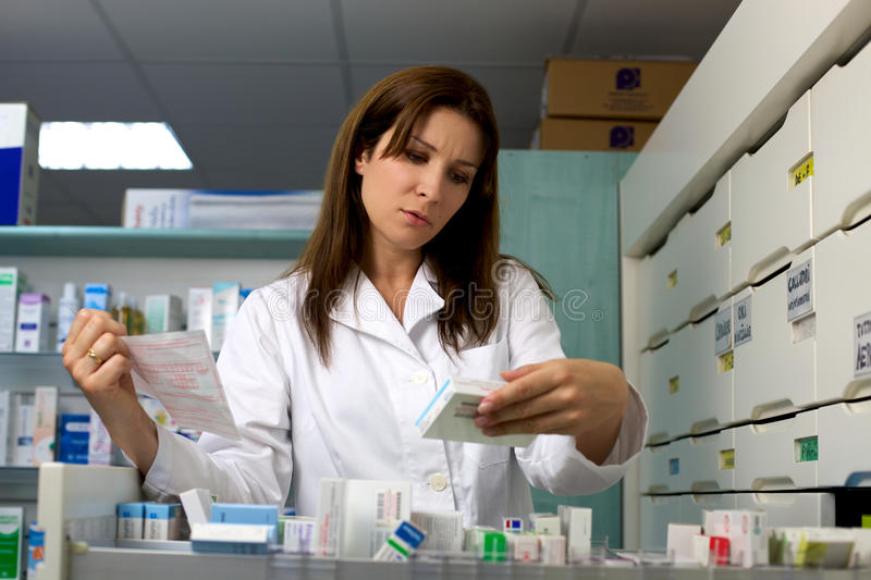 Pharmacist in pharmacy looking medicine and prescription royalty free stock image