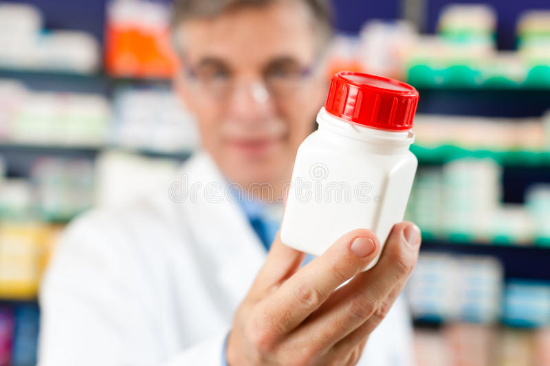 Pharmacist in pharmacy with medicament stock images