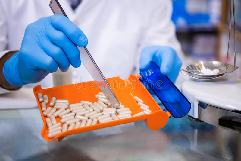 Pharmacist putting pills in container royalty free stock image