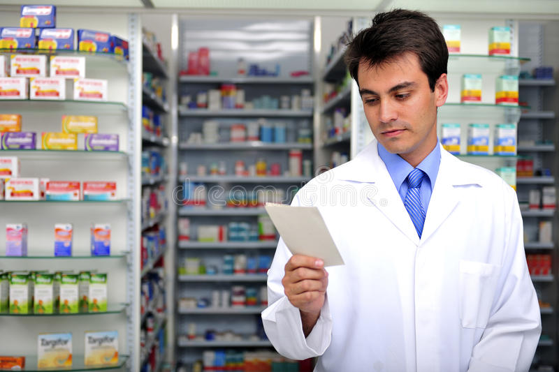 Pharmacist reading prescription at pharmacy royalty free stock image