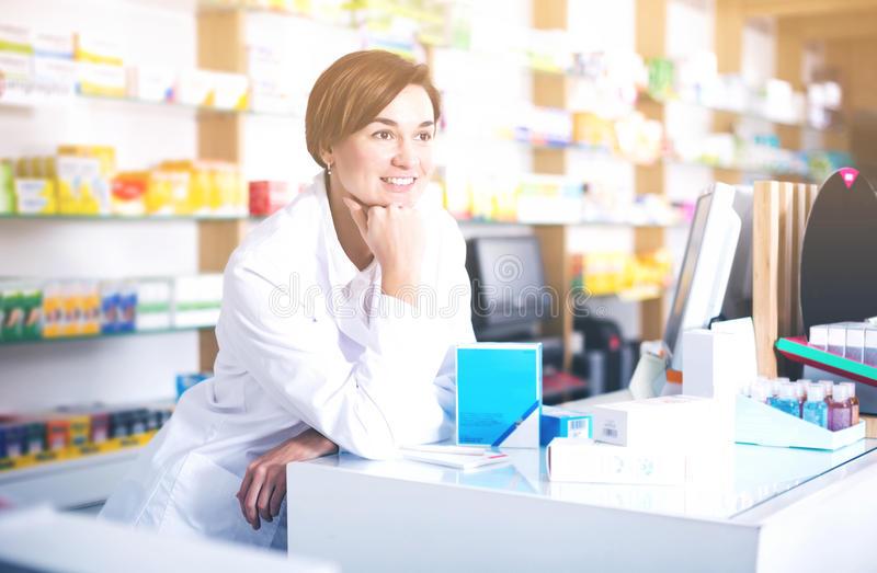 Pharmacist ready to assist in choosing at counter stock photo