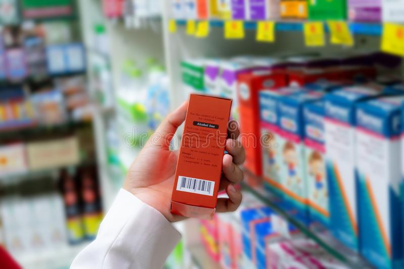 Pharmacist scanning price on a red medicine box with barcode reader in pharmacy store stock photos