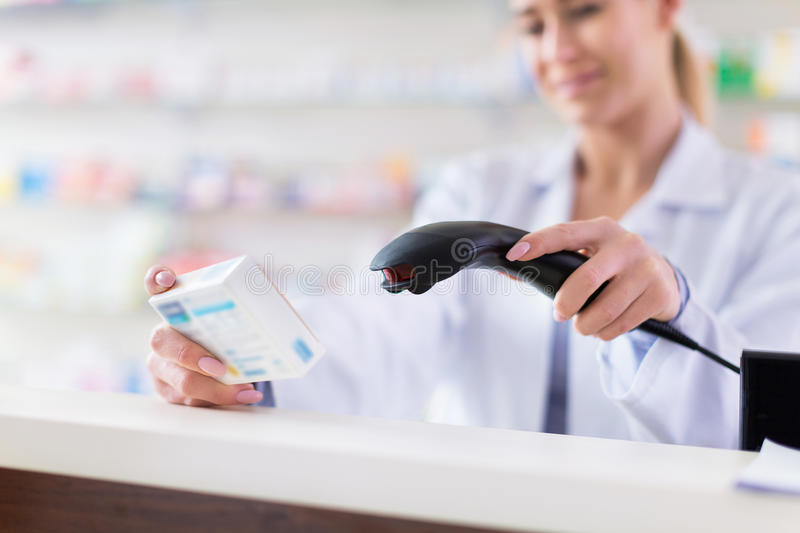 Pharmacist scanning product. In Pharmacy royalty free stock image
