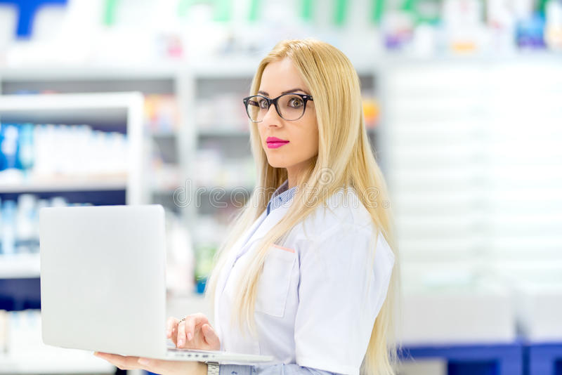 Pharmacist scientist using modern technology in pharmacy. Pharmacist selling antibiotics in drugstore royalty free stock photo