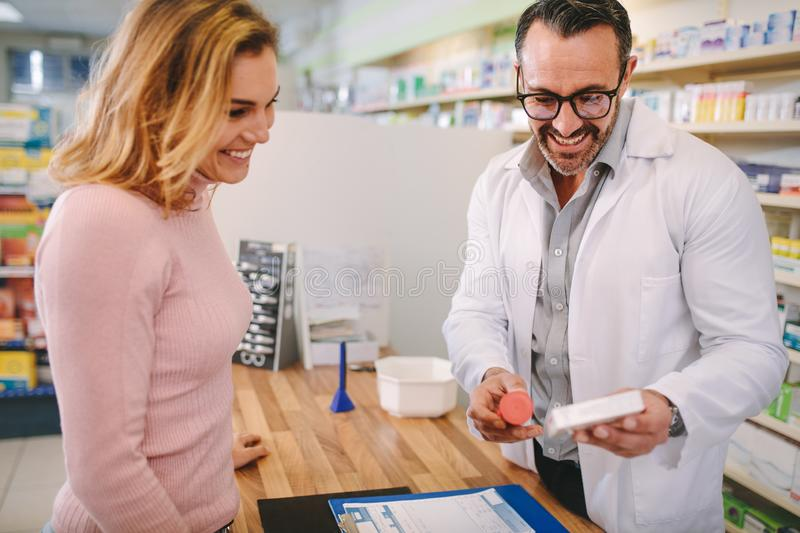 Pharmacist suggesting medical drug to buyer stock photography