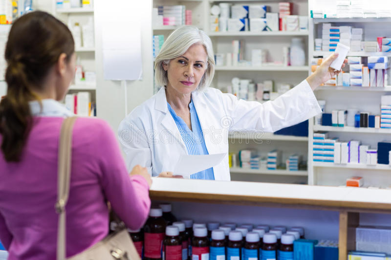 Pharmacist showing the bottle of drug to customer. In pharmacy royalty free stock photography