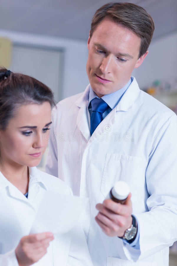 Pharmacist showing medication to his trainee royalty free stock image