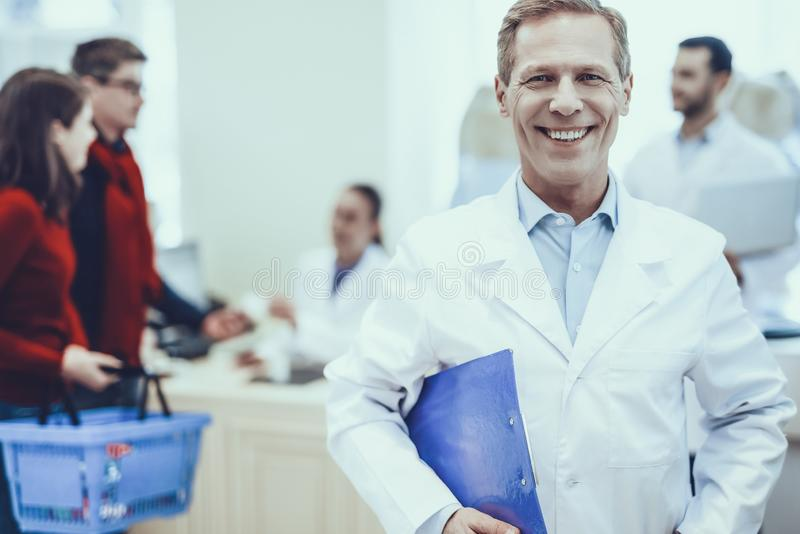 Pharmacists and customers in pharmacy. Pharmacist Smiling into a Camera. Pharmacist is Adult Blonde Man. Other Pharmacists Talking with Customers on Background royalty free stock image