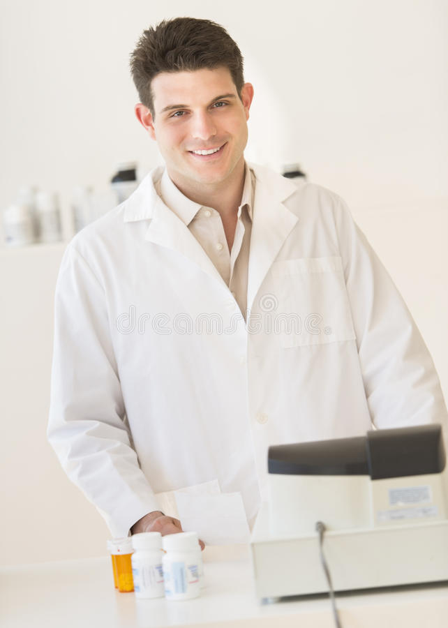 Download Pharmacist Smiling While Standing At Counter In Drug Store Stock Image - Image: 32429773