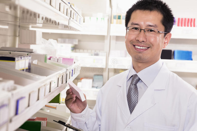 Pharmacist taking down and examining prescription medication in a pharmacy, looking at camera royalty free stock image