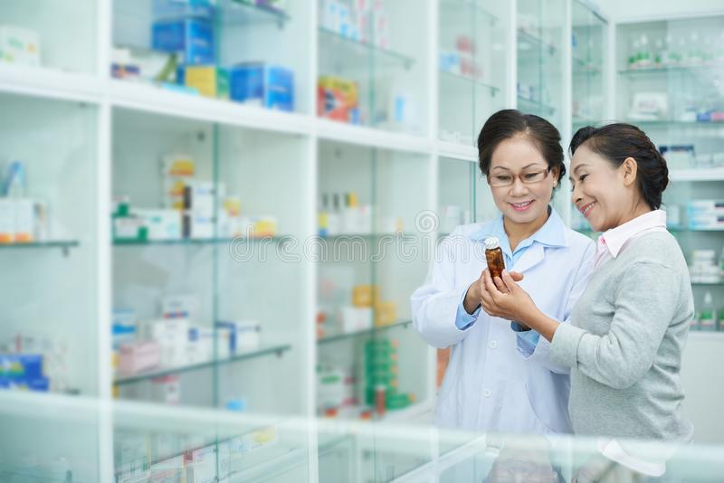 Pharmacist talking with customer stock images