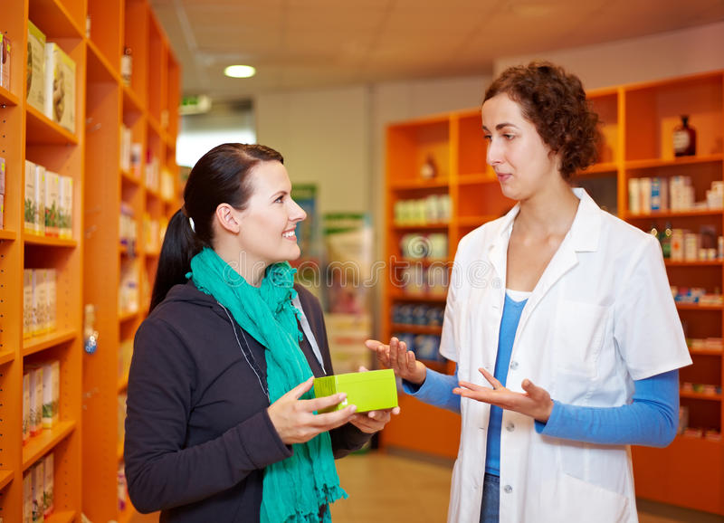 Pharmacist talking to customer royalty free stock image