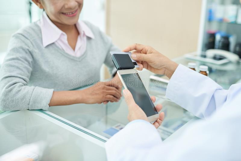 Pharmacist with card reader. Pharmacist using card reader attached to smartphone to accept payment royalty free stock images