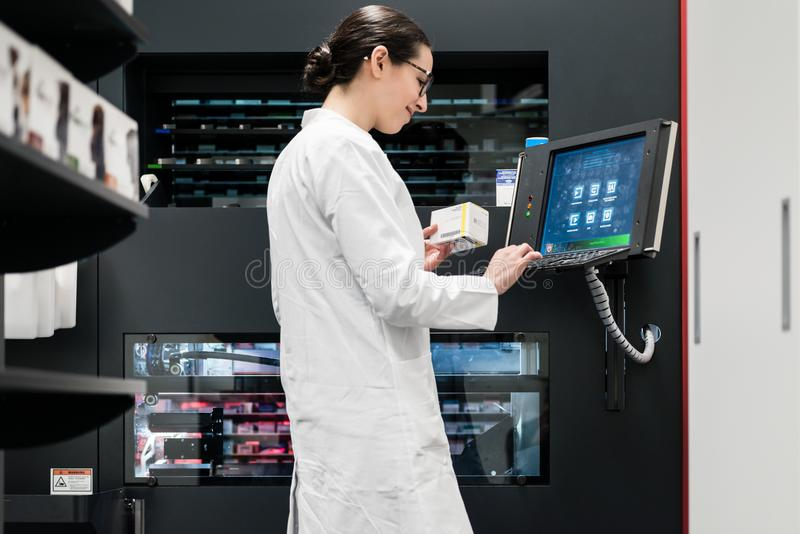 pharmacist using a computer while managing the drug stock in pha stock photography