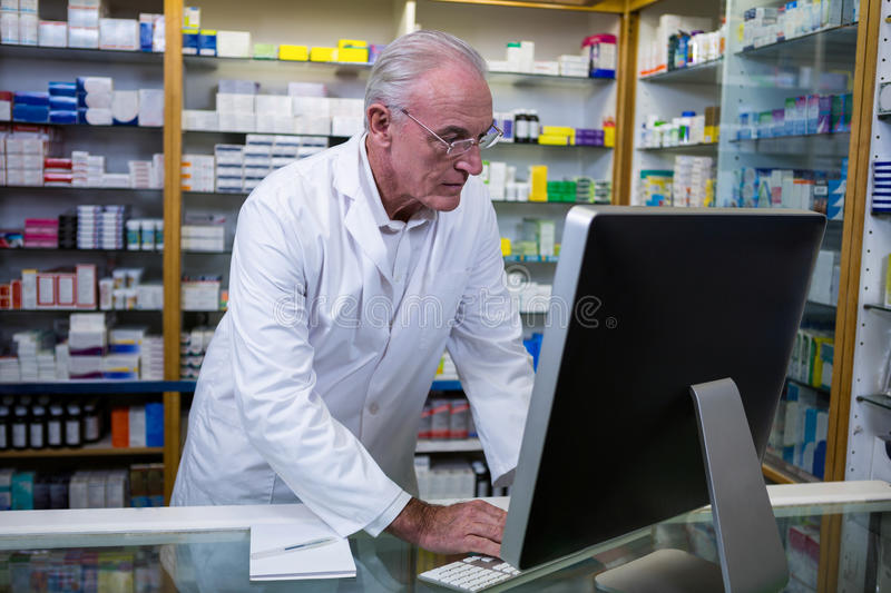 Pharmacist using computer. At pharmacy royalty free stock photography