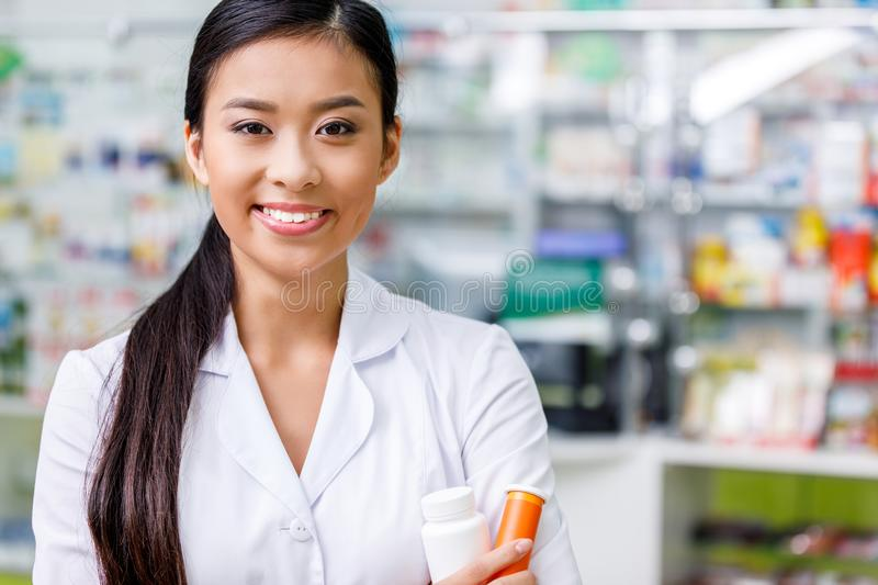 Pharmacist in white coat holding containers with medication and smiling. At camera stock images
