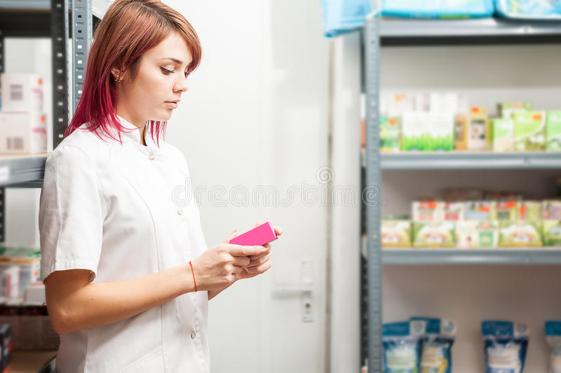 Pharmacist woman in the storage facility next to the shelfs. Healthcare business stock photo