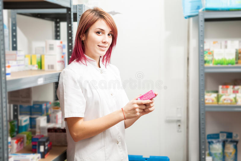 Pharmacist woman in the storage facility next to the shelfs. Healthcare business stock photos