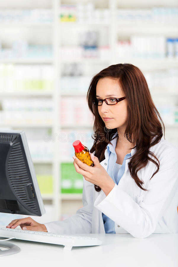 Pharmacist working on her computer. Checking a bottle of pills before dispensing them to a patient stock photos