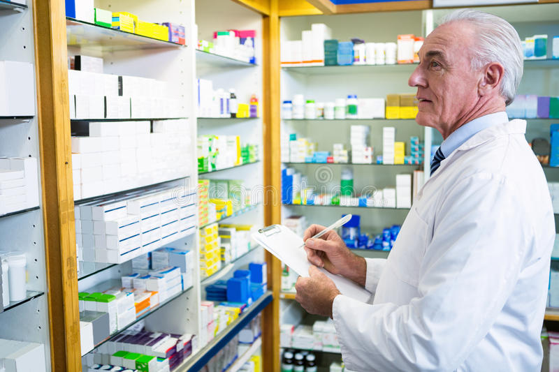 Pharmacist writing on clipboard royalty free stock images