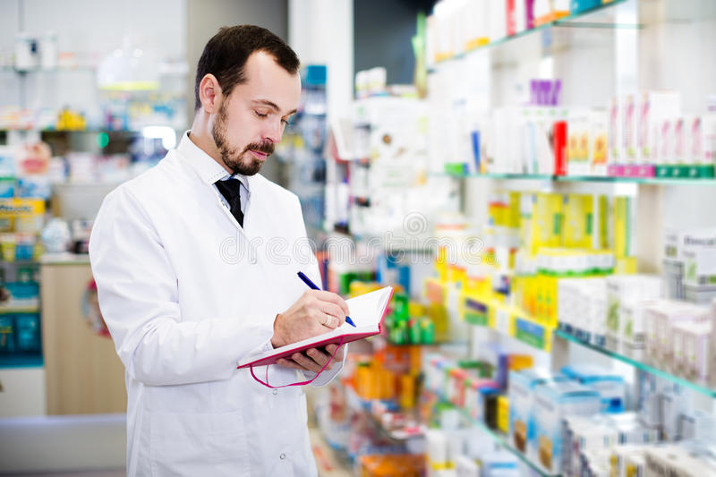 Pharmacist writing down assortment of drugs. Adult man pharmacist writing down assortment of drugs in pharmacy royalty free stock photos