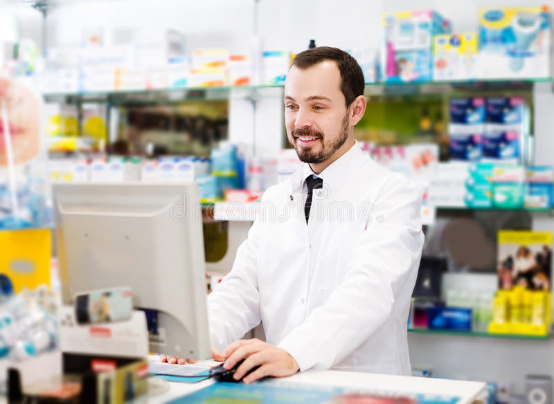 Pharmacist writing down assortment of drugs stock image