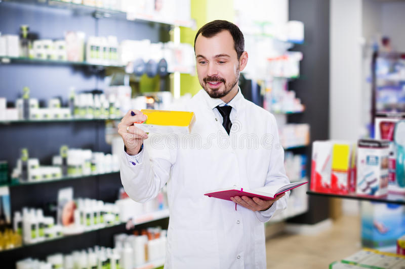 Pharmacist writing down assortment of drugs. Smiling adult man pharmacist writing down assortment of drugs in pharmacy stock photos