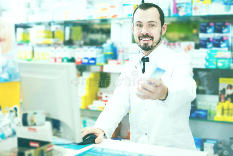 Pharmacist writing down assortment of drugs. Smiling young man pharmacist writing down assortment of drugs in pharmacy royalty free stock image