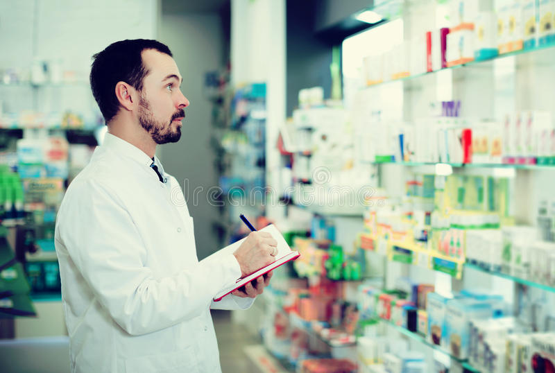 Pharmacist writing down assortment of drugs. Young man pharmacist writing down assortment of drugs in pharmacy royalty free stock photos