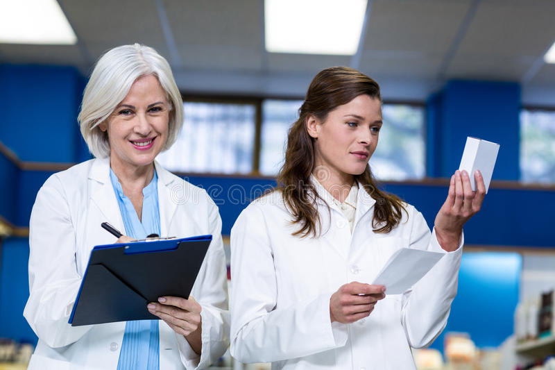 Pharmacists checking and writing prescription for medicine. In pharmacy royalty free stock image
