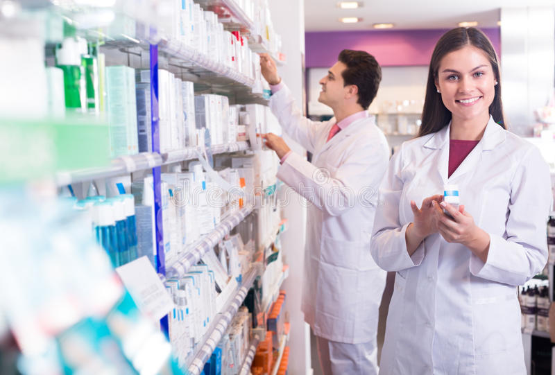 Pharmacists posing in drugstore. Smiling pharmacist and pharmacy worker posing in drugstore stock images