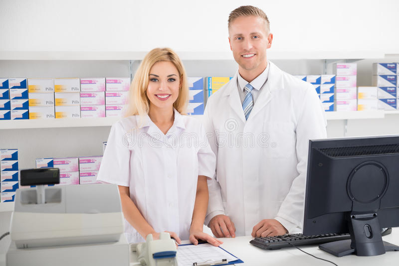 Pharmacists Smiling At Counter In Pharmacy stock photo