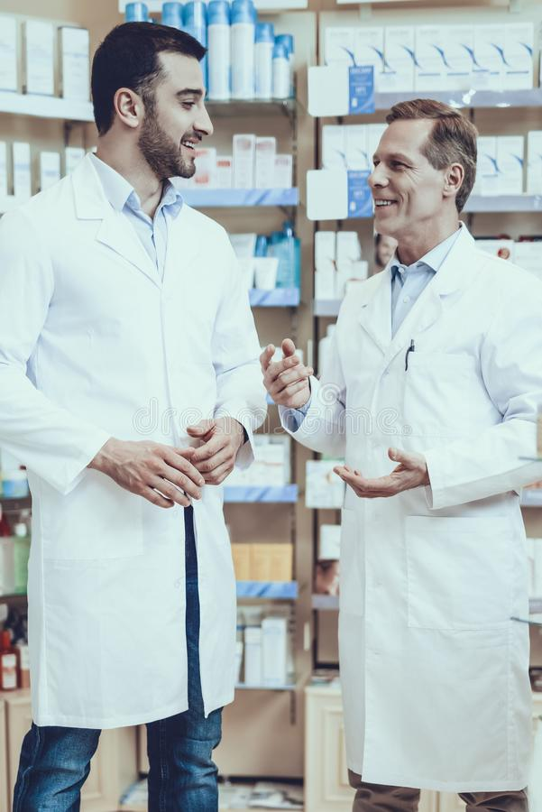 Pharmacists is Talking with Each Other. Two Pharmacists is Talking with Each Other. Pharmacists is a Caucasian Adult Man and Young Guy. Men Wearing a Special royalty free stock image