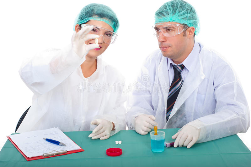 Pharmacists team studying oil capsule stock images
