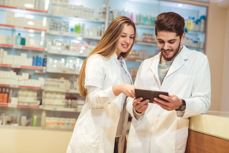 Pharmacists using digital tablet while checking medicine. In pharmacy royalty free stock photo